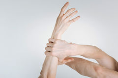 Strong athletes hands demonstrating power in the studio. Fight in details. Flexile strong powerful athletes hands locating in the white colored studio and being Royalty Free Stock Photography