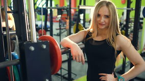 Strong athletic blonde woman smiling and looking into camera in fitness club stock footage