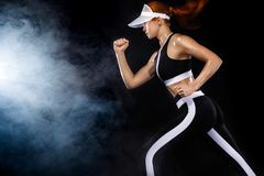 Strong athletic woman sprinter, running on black background wearing in sportswear. Fitness and sport motivation. Run. A Strong athletic, female runner on the stock image