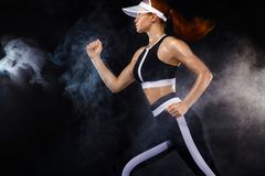 Strong athletic woman sprinter, running on black background wearing in sportswear. Fitness and sport motivation. Run. A Strong athletic, female runner on the stock photos