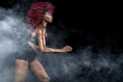 A strong athletic, female sprinter, running at sunrise wearing in the sportswear, fitness and sport motivation concept Stock Photos