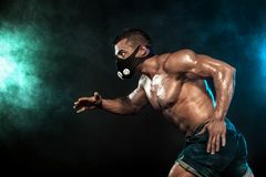 Strong athletic man sprinter in training mask, running, fitness and sport motivation. Runner concept with copy space. Dynamic move Stock Photography