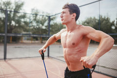 Strong athletic guy sports man stretches expander Royalty Free Stock Photography
