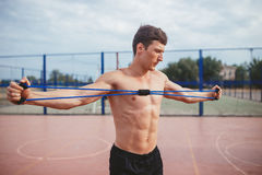 Strong athletic guy sports man stretches expander Stock Image