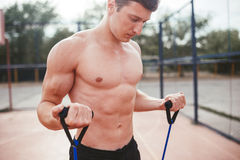 Strong athletic guy sports man stretches expander Stock Photography
