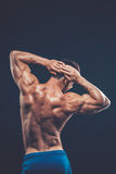 Strong athletic man back on dark background.  Royalty Free Stock Image
