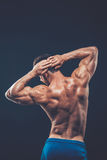 Strong athletic man back on dark background.  Stock Photo