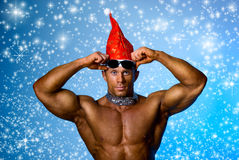 Strong athletic man in a cap of Santa Claus. Royalty Free Stock Image