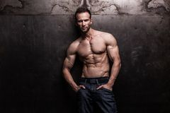 Strong athletic man on dark grunge background. Studio shot of strong athletic man on dark grunge background stock photography