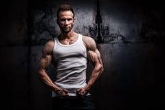 Strong athletic man on dark grunge background stock photos