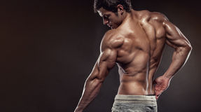 Strong Athletic Man Fitness Model posing back muscles with trice. Strong Athletic Man Fitness Model posing back muscles, triceps, latissimus with copyspace Stock Images