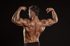Strong Athletic Man Fitness Model posing back muscles, triceps,. Latissimus over black background royalty free stock images