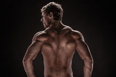 Strong Athletic Man Fitness Model. Posing back muscles, triceps, latissimus over black background Royalty Free Stock Image