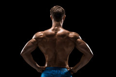 Strong Athletic Man Fitness Model posing back muscles, triceps over black background Stock Photos