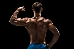 Strong Athletic Man Fitness Model posing back muscles, triceps over black background Stock Image