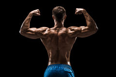 Strong Athletic Man Fitness Model posing back muscles, triceps over black background Royalty Free Stock Photo