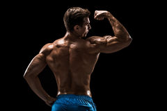 Strong Athletic Man Fitness Model posing back muscles, triceps over black background Royalty Free Stock Image