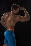 Strong Athletic Man Fitness Model posing back muscles, triceps over black background Stock Photo