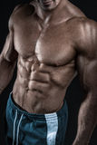 Strong athletic man fitness model showing torso muscles Stock Photography