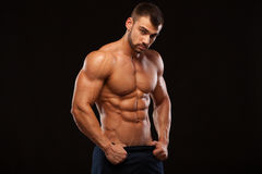 Strong Athletic Man - Fitness Model showing Torso with six pack abs. stands straight and puts his hands in trousers. Isolated on black background with Royalty Free Stock Photos