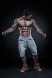 Strong Athletic Man Fitness Model Torso showing big muscles. Over black background royalty free stock photo