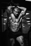Strong Athletic Man Fitness Model Torso showing muscles in gym Stock Photography