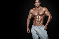 Strong Athletic Man Fitness Model Torso showing muscles. Over black background Stock Images