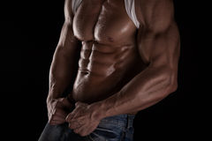 Strong Athletic Man Fitness Model Torso showing six pack abs. Isolated on black background Royalty Free Stock Image