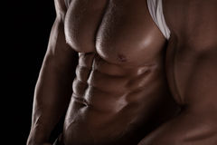 Strong Athletic Man Fitness Model Torso showing six pack abs. Isolated on black background royalty free stock photo