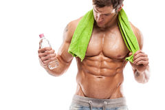 Strong Athletic Man Fitness Model Torso showing six pack abs. Holding bottle of water and towel royalty free stock photography