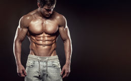Strong Athletic Man Fitness Model Torso showing six pack abs. , c. Strong Athletic Man Fitness Model Torso showing six pack abs. isolated on black background stock photo