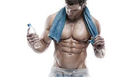 Strong Athletic Man Fitness Model Torso showing six pack abs. Holding bottle of water and towel Stock Image