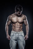 Strong Athletic Man Fitness Model Torso showing six pack abs. Isolated on black background Royalty Free Stock Photos
