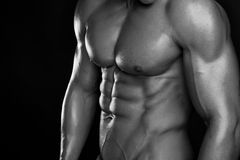 Strong Athletic Man Fitness Model Torso showing six pack abs. Isolated on black background Stock Photo
