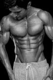 Strong Athletic Man Fitness Model Torso showing six pack abs. Isolated on black background Stock Images