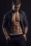 Strong Athletic Man Fitness Model Torso showing six pack abs. Isolated on black background Stock Photos