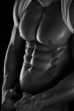 Strong Athletic Man Fitness Model Torso showing six pack abs. Isolated on black background royalty free stock images