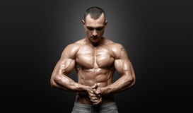 Strong Athletic Man Fitness Model Torso showing six pack abs. Isolated on black background with clipping path Stock Image