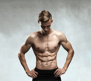 Strong Athletic Man Fitness Model Torso showing six pack abs. Isolated on gray background with clipping path stock photo