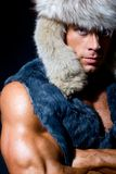 Strong athletic man in a fur cap. Isolated over black background Royalty Free Stock Image