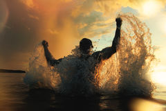 Strong and athletic man jumps out of the water at sunset. Flying a lot of splashing Royalty Free Stock Photo