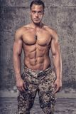 Strong athletic man with naked body in military pants. On concrete wall stock image