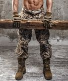 Legs in military uniform. Strong athletic man with naked body in military pants working gloves and rope on concrete wall Royalty Free Stock Photos