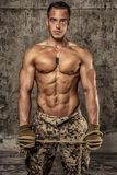 Strong athletic man with naked body in military pants. Working gloves and rope on concrete wall royalty free stock photos