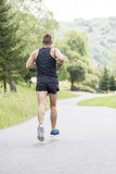 Strong athletic man running down the road, concept of healthy li royalty free stock photos