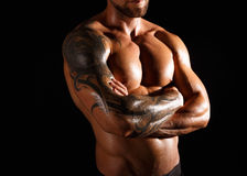 Strong athletic man showes naked muscular body. Athletic man`s torso. Unrecognizable male fitness model show naked muscular body. Strong hands, chest and Stock Image