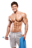 Strong Athletic Man showing big biceps and abdominal muscles. Strong Athletic Man Fitness Model Torso showing six pack abs. holding bottle of water and towel royalty free stock photography