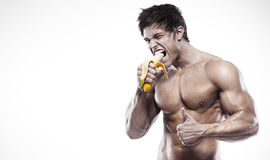 Strong Athletic Man  showing muscular body and eating a banana Royalty Free Stock Image