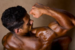 Strong athletic man shows biceps. View top athlete stock images