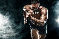Strong athletic man sprinter in training mask, running, fitness and sport motivation. Runner concept with copy space. Dynamic move Stock Images